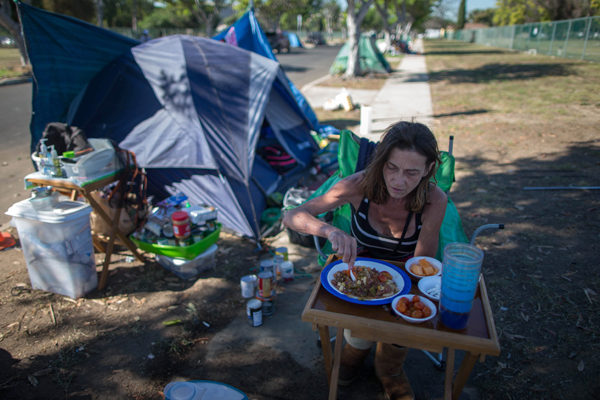 "Stacie McDonough, 51, eats lunch by her tent in a homeless RV and tent encampment near LAX airport in Los Angeles, California, United States, October 26, 2015. McDonough is an army veteran with a college degree who has been homeless for almost 2 weeks. Los Angeles officials last month declared the rising problem of homelessness an ""emergency"" in the city and proposed spending $100 million to provide permanent housing and shelters to help the city's 26,000 indigent. The nation's second-largest city has nearly 18,000 individuals living on the streets, as opposed to shelters. REUTERS/Lucy Nicholson"