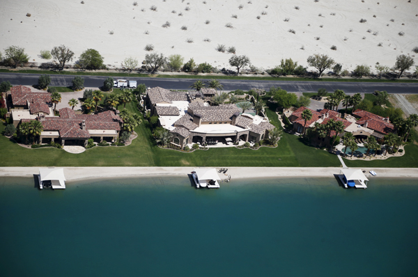Homes with boathouses built around an artificial lake are seen in Indio, California April 13, 2015. California's cities and towns would be required to cut their water usage by up to 35 percent or face steep fines under proposed new rules, the state's first-ever mandatory cutbacks in urban water use as the state enters its fourth year of severe drought. Communities where residential customers use more than 165 gallons of water per person per day would have to cut back by 35 percent. Picture taken April 13, 2015. REUTERS/Lucy Nicholson - RTR4XD3S